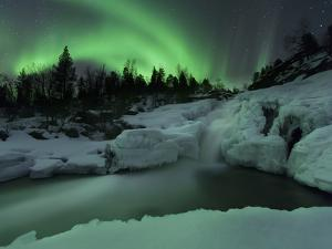 A Wintery Waterfall And Aurora Borealis Over Tennevik River, Norway by Stocktrek Images