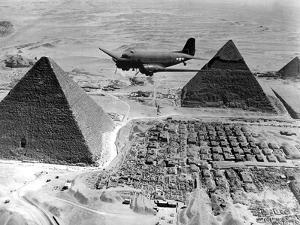An Air Transport Command Plane Flies Over the Pyramids in Egypt by Stocktrek Images