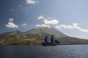 An Indonesian Pinisi Schooner Sails Near a Remote Volcanic Island by Stocktrek Images