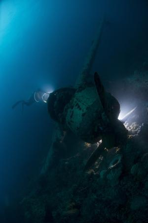 Diver Exploring the Wreck of a Japanese Navy Seaplane in Palau, Micronesia by Stocktrek Images