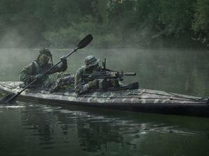 Navy SEALs Navigate the Waters in a Folding Kayak During Jungle Warfare Operations by Stocktrek Images
