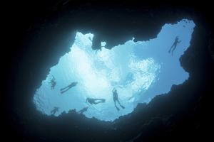 Snorkelers Swim Above a Blue Hole on Palau's Barrier Reef by Stocktrek Images