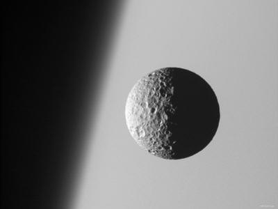 This Amazing Perspective View Captures Battered Moon Mimas Against the Hazy Limb of Planet Saturn