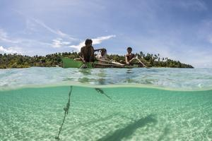 Young Villagers Fish Off their Outrigger Near a Remote Island in Indonesia by Stocktrek Images