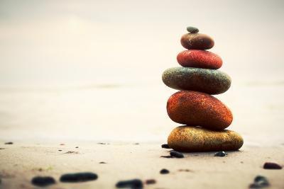 Stones Pyramid on Sand Symbolizing Zen, Harmony, Balance. Ocean in the Background-Michal Bednarek-Photographic Print