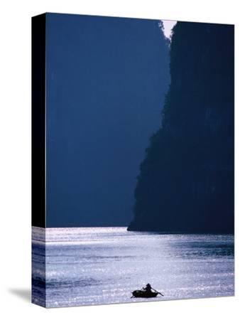Woman Navigates Among Magnificent Limestone Islands of Halong Bay, Halong Bay, Quang Ninh, Vietnam