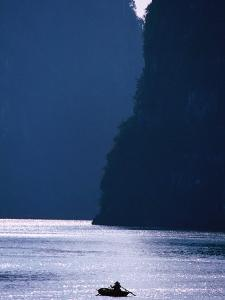 Woman Navigates Among Magnificent Limestone Islands of Halong Bay, Halong Bay, Quang Ninh, Vietnam by Stu Smucker