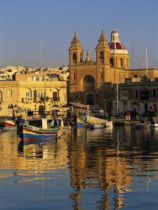 Harbour with Luzzu Fishing Boats and Marsaxlokk Parish Church at Sunrise, Marsaxlokk, Malta, Medite by Stuart Black