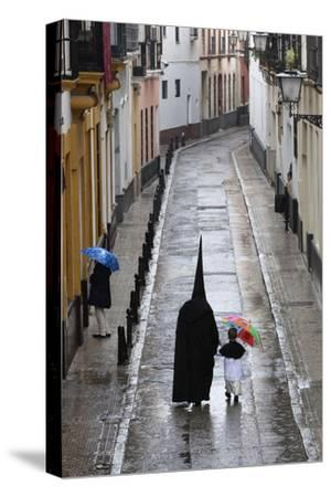 Penitents During Semana Santa (Holy Week) Along Rainy Street, Seville, Andalucia, Spain, Europe