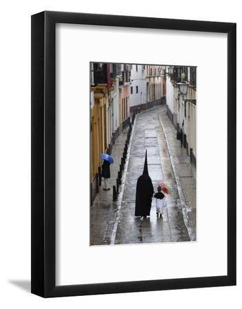 Penitents During Semana Santa (Holy Week) Along Rainy Street, Seville, Andalucia, Spain, Europe