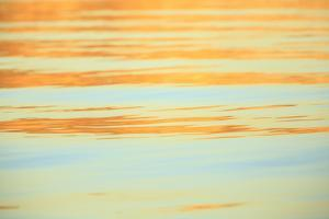 Abstract of water ripples in orange and blue. by Stuart Westmorland