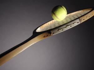 Studio Shot of Tennis Ball on Top of Tennis Racket