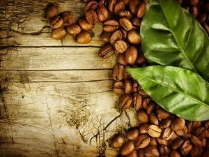 Coffee Beans Over Wood Background by Subbotina Anna