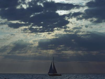 Sunlight Breaks Through a Cloudy Sky onto a Sailboat at Sea-Todd Gipstein-Photographic Print
