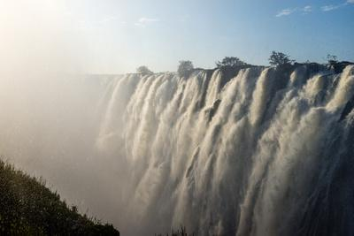 https://imgc.artprintimages.com/img/print/sunlight-catches-the-cascading-pillars-of-the-zambezi-river-as-they-pour-over-victoria-falls_u-l-pyxzmo0.jpg?p=0