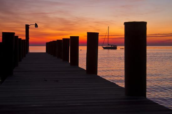 Sunrise on the Water with an Empty Dock and a Sailboat in the Distance of Tilghman Island, Maryland-Karine Aigner-Photographic Print