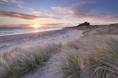 Sunrise over Bamburgh Beach and Castle from the Sand Dunes, Northumberland, England. Spring (March)-Adam Burton-Photographic Print