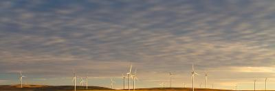 Sunset Light Shining On Wind Turbines Spinning In A Wheat Field-Greg Winston-Photographic Print