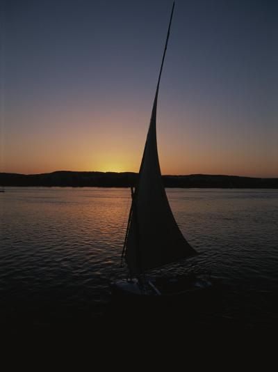 Sunset Outlines the Curve of a Felucca Sail on the Nile River-Stephen St^ John-Photographic Print