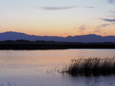 https://imgc.artprintimages.com/img/print/sunset-over-a-peaceful-lake-with-silhouette-of-mountains_u-l-q10x7gw0.jpg?p=0