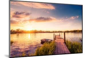 Sunset over the Lake in the Village. View from a Wooden Bridge, Image in the Orange-Purple Toning