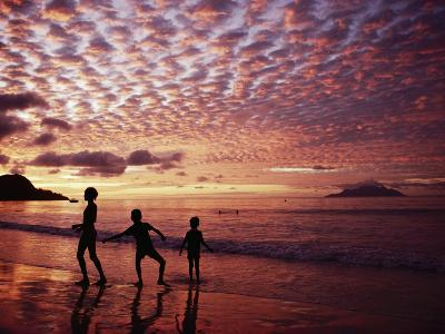 Sunset Reddens a Cloudy Sky as Silhouetted Children Play on the Beach-Steve Raymer-Photographic Print