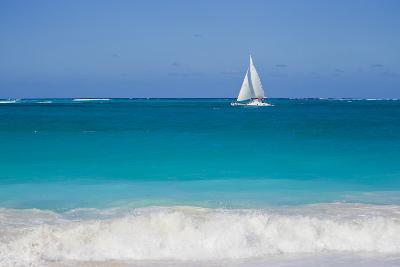 Surf Surges onto a Beach as a Sailboat Passes Offshore-Mike Theiss-Photographic Print