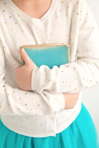 Close Up of Young Girl Holding Book by Susannah Tucker