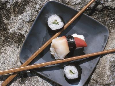 Sushi and Chopsticks Beside Rushing Water--Photographic Print