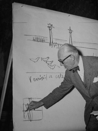 Swiss Architect Le Corbusier Standing on Stage with Notes in His Hand and Drawing on Sketch Pad--Photographic Print