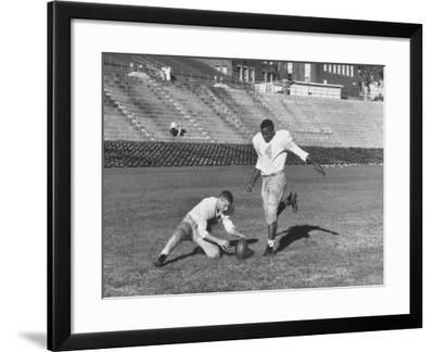 Syracuse Football Player Chuck Zimmerman Holding the Ball to Be Kicked by Teammate Jim Brown-Peter Stackpole-Framed Premium Photographic Print