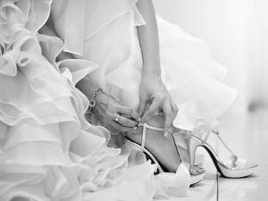 The Bride is Putting on Her Shoes for the Wedding Day by szefei