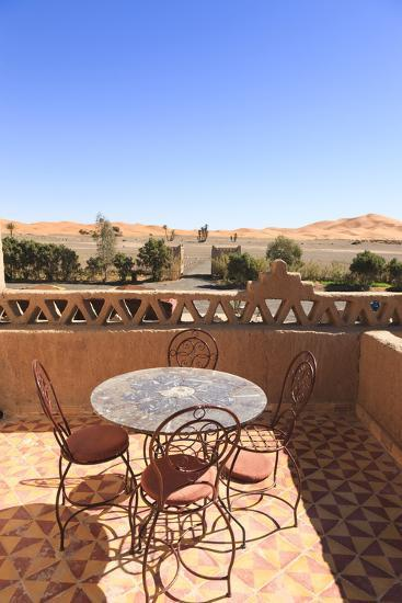Table and Chairs on a Terrace of a Kasbah Hotel with View to the Dunes of the Erg Chebbi, Morocco-Frank Lukasseck-Photographic Print