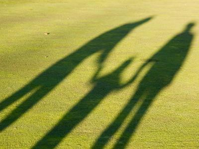 Tall Shadows Loom on the Greens of a Golf Course-Stacy Gold-Photographic Print