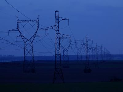 Tall Towers Supporting Power Lines in a Dark Blue Sky--Photographic Print