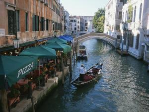 A Gondolier Passes a Restaurant on a Canal in Venice, Italy by Taylor S^ Kennedy