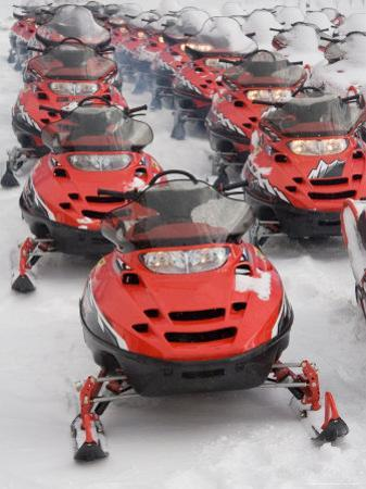 A Large Group of Snowmobiles Sit Waiting for Action by Taylor S. Kennedy