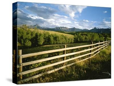 A Rustic Scene of a Fence with Mountains in the Distance in Colorado