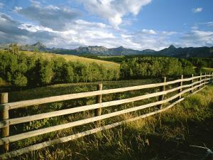 A Rustic Scene of a Fence with Mountains in the Distance in Colorado by Taylor S. Kennedy