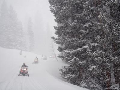 A Small Group of Snowmobilers Turn a Corner in a Snowstorm by Taylor S. Kennedy