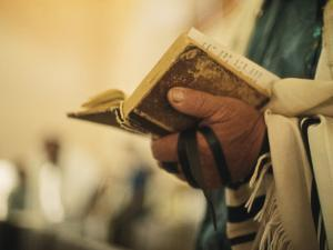 Man Holding a Prayer Book and Tefillin During a Synagogue Service, Israel by Ted Spiegel