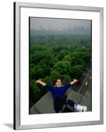 Comedian Jerry Seinfeld Perching Precariously on Roof Ledge Overlooking Central Park