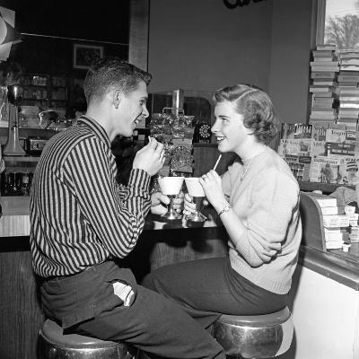 Teen Couple on Stools at Soda Fountain Drinking Shakes and Smiling at Each Other-H^ Armstrong Roberts-Photographic Print