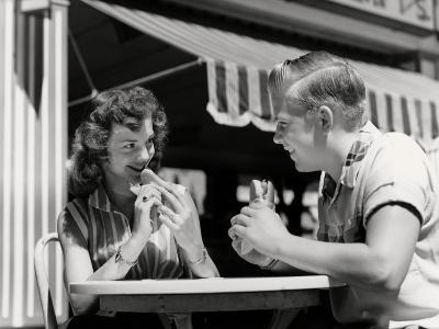 Teenage Couple Eating Hotdogs Outside at Refreshment Stand Table-H^ Armstrong Roberts-Photographic Print