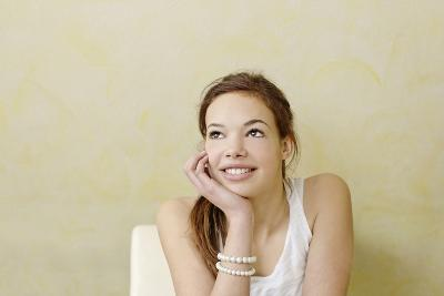 Teenage Girl Sitting at the Table, Smiling, Portrait-Axel Schmies-Photographic Print