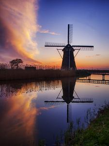 Netherlands, Kinderdijk, Sunrise along the canal with Windmills by Terry Eggers
