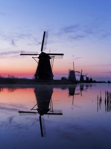 Netherlands, Kinderdijk, Windmills at Sunrise along the canals. by Terry Eggers