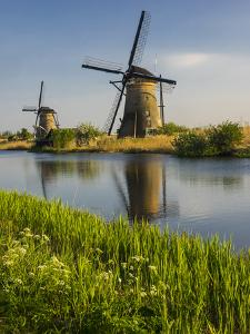 Netherlands, Kinderdijk, Windmills with evening light along the canals. by Terry Eggers