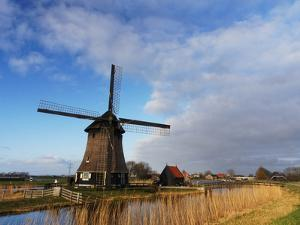 Netherlands, Nord Holland, Windmill along canal by Terry Eggers