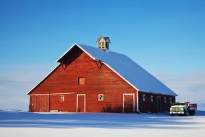 USA, Idaho, Old Red Barn and Truck after Snowstorm by Terry Eggers